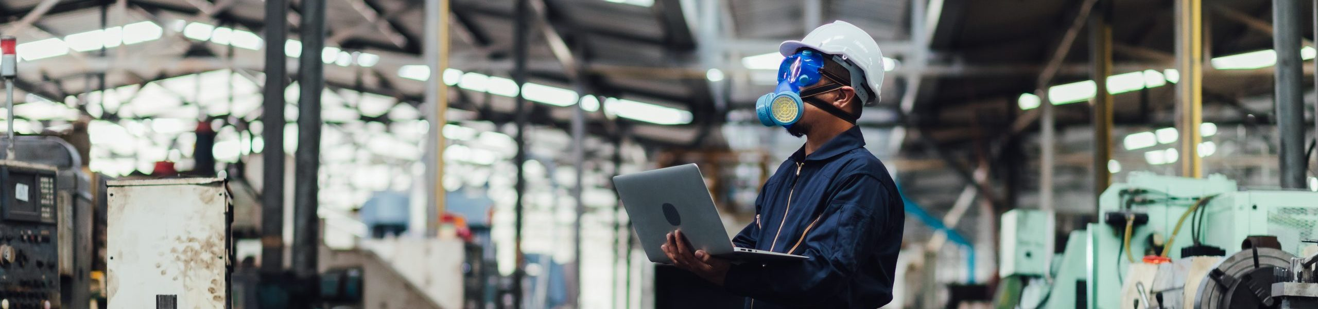 Officials from the Department of Hazardous substances control bureau is investigating the leak of a hazardous chemical in a chemical plant. Man with protective mask and computer laptops in factory